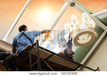 unidentified people wrappers tinting a glass house window with tinted foil or film using foggy spray