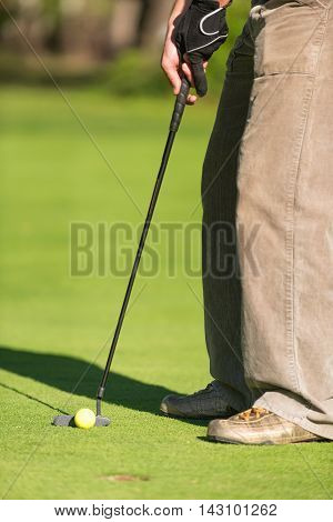 Golfer putting selective focus, vertical image, toned image