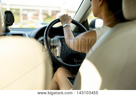 Concept dangerous Woman with cell phone on her lap while driving