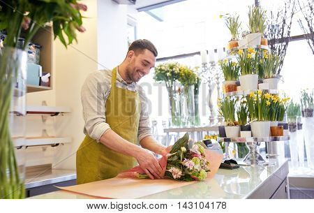 people, shopping, sale, floristry and consumerism concept - happy smiling florist man wrapping flowers in paper at flower shop