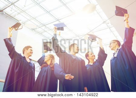 education, graduation and people concept - group of happy students or bachelors in gowns waving mortarboards at school