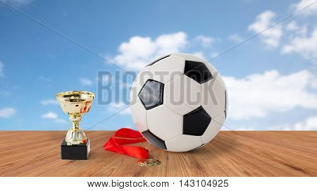 sport, achievement, championship, competition and success concept - close up of football or soccer ball with golden medal and cup over blue sky and wooden floor background
