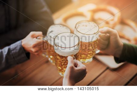 people, leisure and drinks concept - close up of hands clinking beer mugs at bar or pub