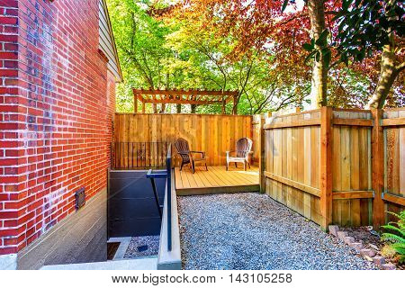 Small Wooden Back Deck With Two Chairs.