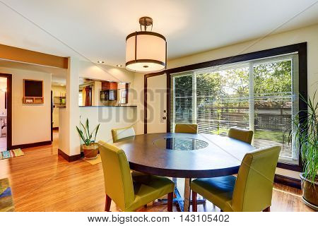 Nice Dining Area With Round Table And Green Chairs.
