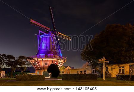 De Molen windmill of Foxton New Zealand with it's night color lights on.