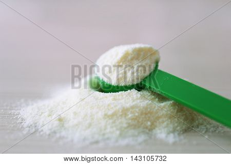 Baby milk formula in green spoon on wooden background