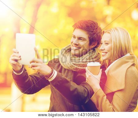 travel, tourism, modern technology, holidays and dating concept - couple taking photo picture with tablet pc camera in autumn park