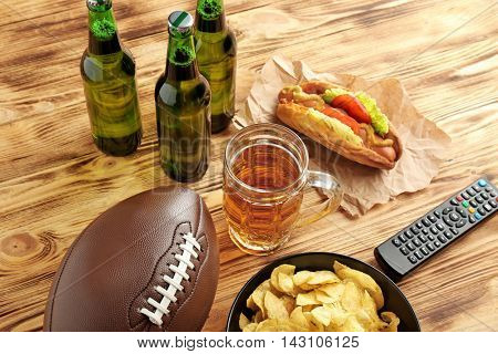 Glass of beer, bottles and snack on wooden background