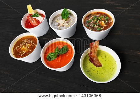 Variety of restaurant hot dishes, healthy food. Japanese miso soup, asian fish soup, russian borscht, english pea soup with bacon, mushroom soup, spanish gazpacho at black rustic wood