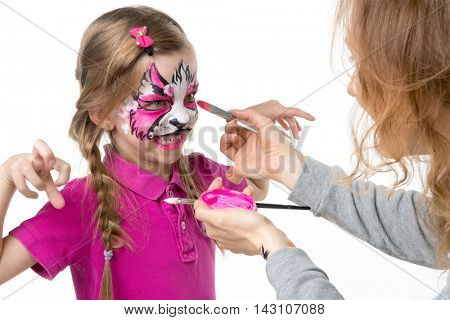 growling little girl getting her face painted with watercolors by artist