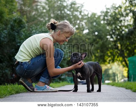She communicates with the dog while walking. Street of the city summer. French Bulldog in black with a collar and leash