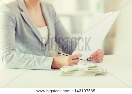 business, finance, tax and people concept - close up of woman hands with us dollar money and tax report paper form