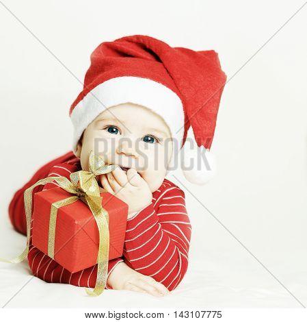 Happy baby in Santa hat on light background
