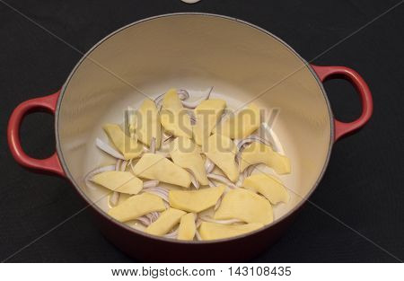 potatoes and sliced onions and placed with oil in a red casserole. black background