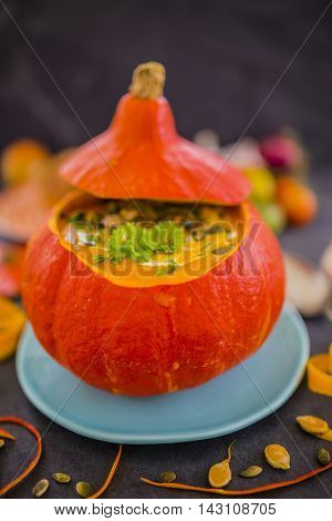 Cream of pumpkin soup with pumpkin seeds, white cream, vegetables in hollowed-out pumpkin on black stone table.