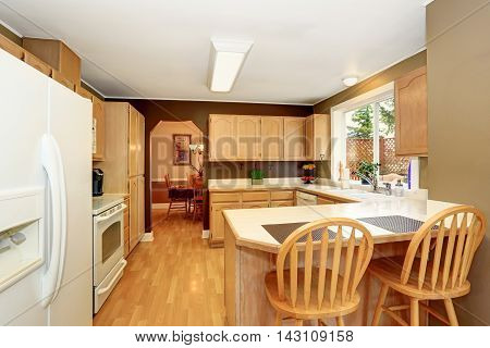 Kitchen Room With Light Brown Cobinets And Tile Counter Top.