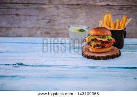 Tasty street food grilled beef burger in crispy shortbread with lettuce and mayonnaise served on small cutting board a rustic wooden table with copyspace.