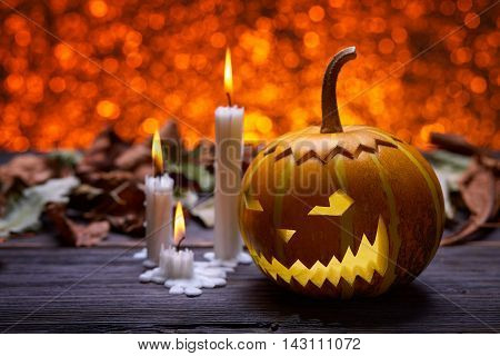 Pumpkin for Halloween, lamp pumpkin, antique wood, celebrating halloween, smiley on a pumpkin, paraffin candles, bright background, burning candles, autumn dry leaves