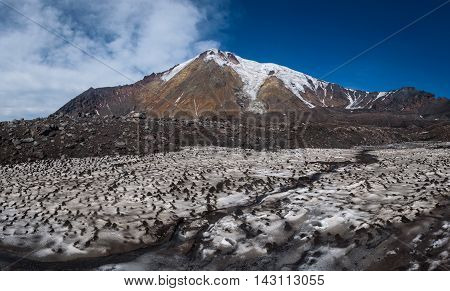 Icy glaciers on the slopes of Tolbachik Volcano viewed over a field with snow covered with sand and ash, Kamchatka, Russia.