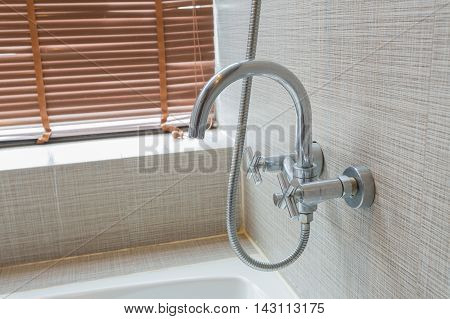 The faucet in the bathtub in modern bathroom interior concept.