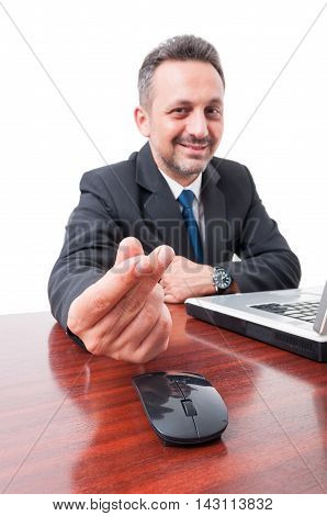 Businessperson On Desk Doing Money Gesture