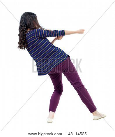 back view of standing girl pulling a rope from the top or cling to something. girl  watching. Rear view people collection.  backside view of person.  Isolated over white background. Long-haired curly