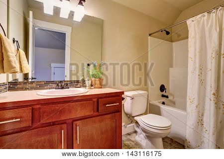Bathroom With White Bath Tub, Tile Floor And Vanity Cabinet