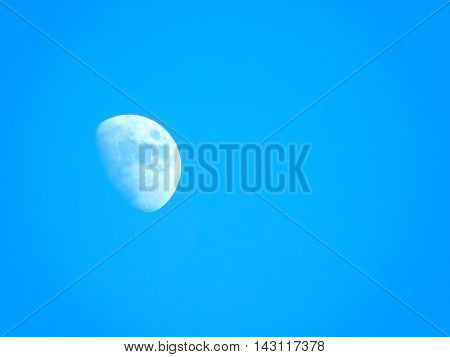 The moon in the colourful blue skies .