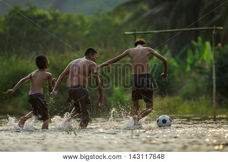 Boy playing football with kicking soccer ball in the waterDisadvantaged