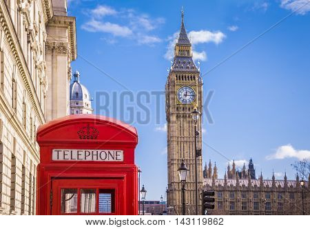 Traditional red british telephone box and Big Ben at Parliament Square with blue sky and clouds - London, UK