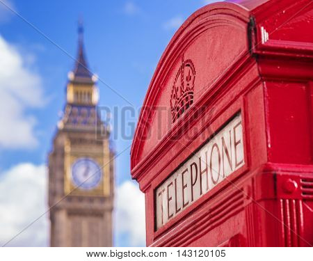 Iconic red british telephone box with Big Ben at the background on a sunny afternoon with blue sky and clouds - London, UK