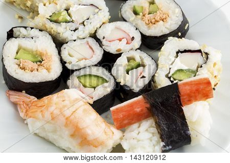 Plate of sushi, with soy sauce and chopsticks, over white background