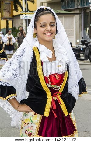 QUARTU S.E., ITALY - September 15, 2013: Wine Festival in honor of the celebration of St. Helena - Sardinia - portrait of a beautiful smiling girl in costume Sardinian folk group Saint Lucia in Settimo San Pietro