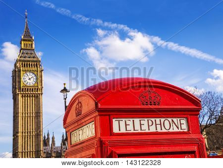 London, England - Old Red Telephone box and Big Ben with blue sky - United Kingdom
