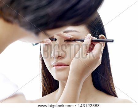 makeup artist working on eyeliner of a young asian model isolated on white background.