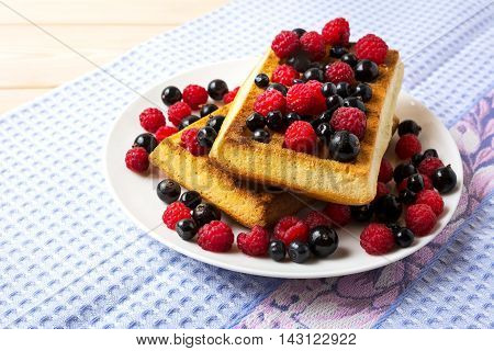 Soft Belgian waffles with blueberry raspberry and blackcurrant. Breakfast waffles with fresh berries.