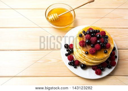 Breakfast pancakes with honey and fresh berries. Stack of homemade pancakes served with blueberry raspberry and blackcurrant.