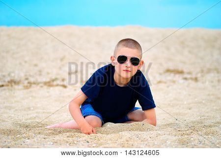 Little boy with sunglasses playing in the sand on the beach
