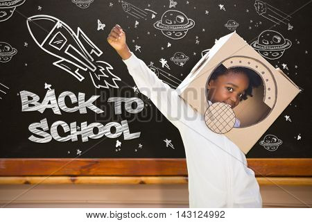Boy playing as an astronaut in a park against blackboard