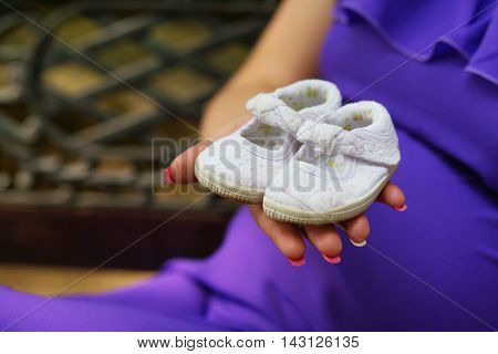Pregnant Woman Holding Baby Shoes On Her Hand