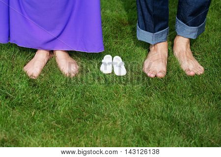 Young Pregnant Couple Feet Barefoot On Green Gras