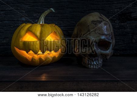 Halloween pumpkin head jack lantern with scary evil faces and human skull over wooden background in darkness night