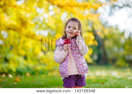 Little kid girl at beautiful autumn park. child having fun with colorful foliage and enjoying golden year season.