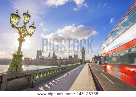 London, England - Iconic Red Double Decker bus going through Westminster Bridge with Big Ben at background