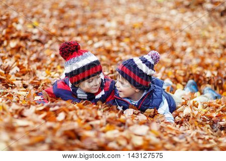 Two little twin boys lying in autumn leaves in colorful clothing. Happy siblings kids having fun in autumn forest or park on warm fall day. With hats and scarfs