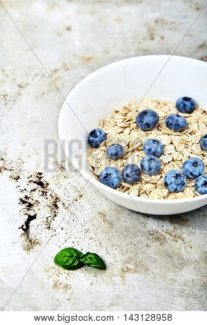 Raw oat flakes topped fresh blueberries in white bowl. Perfect ingredients for delicious and healthy breakfast. Dietary tasty food on metal, grunge backg with mint near it. Vitamin and energy booster