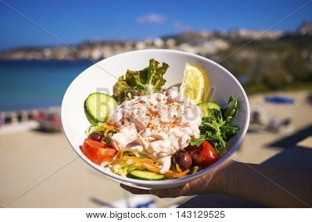 Fresh prawn salad in white bowl with mixed lettuce leaves, cucumber, tomato lemon and mayonnaise on the beach