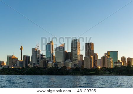 Sydney CBD skyscrapers with Sydney Tower and Royal Botanic Garden view on sunset with sun reflecting from windows. Modern urban cityscape with office buildings