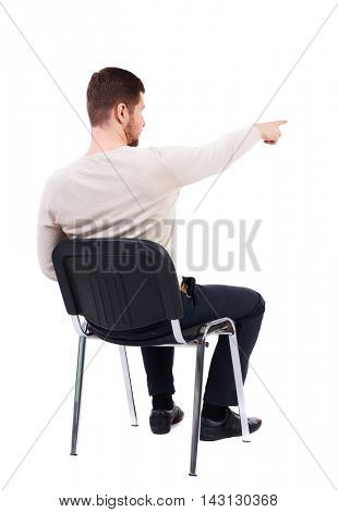 back view of young business man sitting on chair and pointing. Rear view people collection. The bearded man in a white warm sweater sits on a chair and shows his hand forward. Side view.